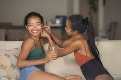 两名妇女生活方式自然画象,一起把耳环放的一个愉快的女孩在她的年轻美丽和异乎寻常的女朋友smi上 库存图片