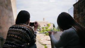 两名妇女由台阶他们中的一个坐画 然后另一名妇女得到照片照相机 股票视频