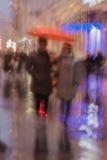 两名妇女的抽象背景在伞,在路的步行下在城市在雨中 轻的照明 故意 免版税库存照片