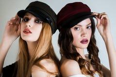 两名妇女盖帽的和有在紧接看照相机的白色背景的明亮的构成的 时尚,化妆用品,面部关心 免版税库存图片