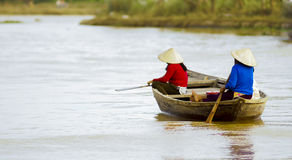 两名妇女荡桨在星期四好的妙语河的一条小船 免版税库存图片