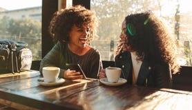 两名妇女获得乐趣在咖啡店 图库摄影
