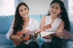 两名妇女获得演奏尤克里里琴和在家微笑为的乐趣 免版税库存照片