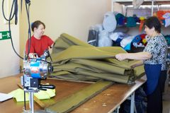 两名妇女裁缝解开织品卷进一步tailori的 免版税库存图片