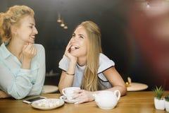 两名妇女说闲话在一次会议上在咖啡馆 免版税库存照片