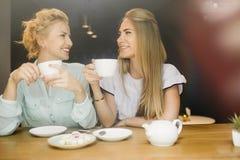 两名妇女说闲话在一次会议上在咖啡馆 图库摄影