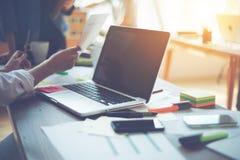 两名妇女谈论一个新的数字式项目在办公室 膝上型计算机和文书工作在桌上 库存照片
