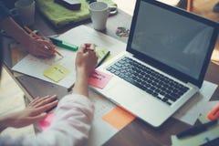 两名妇女谈论一个新的项目在办公室 膝上型计算机和文书工作在桌上 免版税库存照片