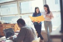 两名妇女谈论工作计划在办公室 膝上型计算机人工作 Coworking和露天场所办公室 库存图片