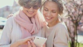 两名妇女谈论照片在智能手机 春天画象在公园 网络营销,MLM事务 股票视频