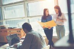 两名妇女谈论销售计划在办公室 膝上型计算机人工作 Coworking和露天场所办公室 免版税库存图片