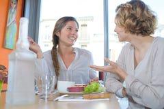 两名妇女谈话在咖啡馆在购物以后 库存图片