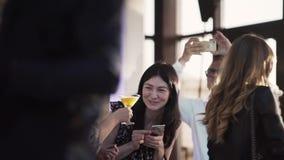 两名妇女谈话并且喝 在他们旁边的年轻人拍在智能手机的照片 股票录像