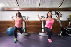 两名妇女锻炼一腿刺抵抗带 库存图片