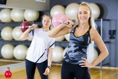 两名妇女画象有kettlebells的在健身健身房 免版税库存图片