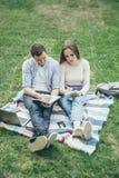 两名学生为研讨会做准备坐草 在线教育 免版税库存照片