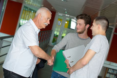 两名学生和他们的讲师走廊的 免版税图库摄影