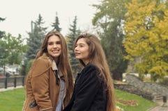两名学生在秋天公园走并且获得乐趣 库存照片