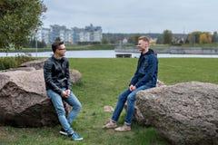 两名学生坐和谈话,城市风景和大厦在背景中 免版税图库摄影