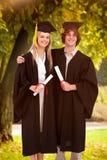 两名学生的综合图象毕业生长袍的并肩 库存图片