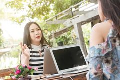两名少年妇女在咖啡店用途膝上型计算机一起见面在船尾 库存图片