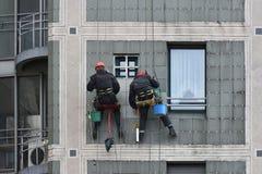 两名工作者固定门面垂悬 库存图片