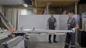 两名工作者在切割机上把木颗粒盘放在家具制造业车间  股票录像