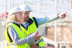 两名工作者外面与在建造场所的一种片剂一起使用 库存照片