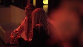 两名年轻俏丽的妇女坐沙发在与咖啡的窗口旁边 影视素材