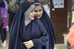 两名年轻回教妇女在城市,设拉子,伊朗附近走 图库摄影