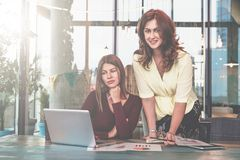 两名年轻女实业家在办公室工作 第一名妇女坐在桌上并且看膝上型计算机屏幕 免版税库存图片