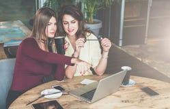 两名年轻女实业家在咖啡馆坐在桌上,女孩指向膝上型计算机屏幕 库存照片