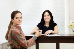 两名年轻微笑的妇女画象  牙齿诊所的管理员和患者 库存图片