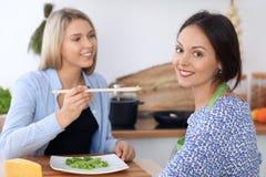 两名年轻愉快的妇女在厨房里烹调 朋友获得乐趣,当preapering健康和鲜美膳食时 免版税库存图片
