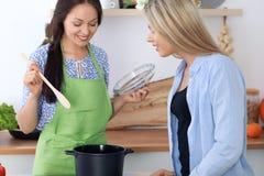 两名年轻愉快的妇女在厨房里烹调 朋友获得乐趣,当preapering健康和鲜美膳食时 库存图片