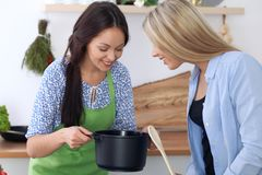 两名年轻愉快的妇女在厨房里烹调 朋友获得乐趣,当preapering健康和鲜美膳食时 图库摄影