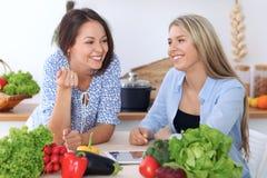 两名年轻愉快的妇女由片剂计算机和信用卡做网上购物 朋友在Th烹调 图库摄影