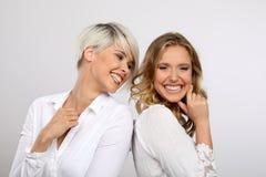 两名年轻白肤金发妇女微笑 免版税库存图片