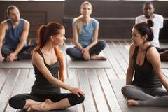 两名年轻美丽的适合妇女谈话在小组瑜伽训练 库存图片