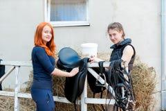 两名微笑的十几岁的女孩骑马者清洗黑皮革马 免版税库存图片