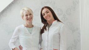两名微笑的妇女-一件白色外套的金发碧眼的女人 年轻专家是美容师 股票视频