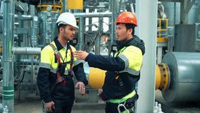 两名微笑的金属工作者谈论工作在生产设备站点 股票视频