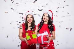两名性感的妇女红色圣诞节圣诞老人假日帽子的坐与发光穿闪耀的晚礼服的g五彩纸屑的地板 库存图片