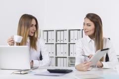 两名愉快的女实业家在有片剂的办公室 图库摄影
