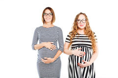 两名愉快的孕妇接触他们的腹部 图库摄影