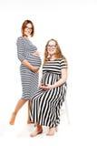 两名愉快的孕妇是玻璃接触他们的腹部 图库摄影