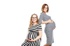 两名愉快的孕妇是玻璃接触他们的腹部 免版税库存图片