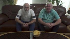 两名成熟老人坐棕色皮革沙发看着电视 朋友向前同时倾身,等待 股票录像