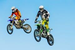 两名摩托车骑士特写镜头从在蓝天背景的一座山跳跃  图库摄影