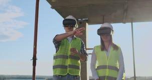 两名现代建筑工人画象的腰部使用形象化VR的齿轮的在站点,拷贝空间的项目 股票视频